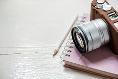 Classic camera put on closed notebook on white table Royalty Free Stock Photos