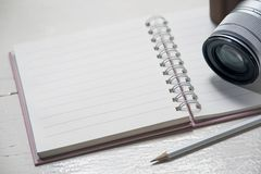 Classic camera put on blank notebook with pencil on white table Royalty Free Stock Photography