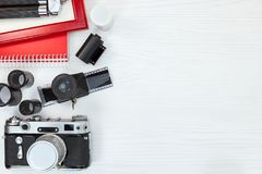 Classic camera, red photo frame, notepad and tripod on white woo Stock Photo