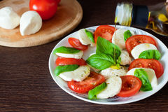 Olive Oil Pouring On Caprese Salad Stock Photo