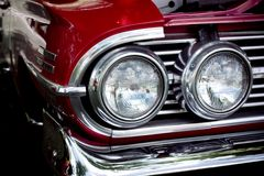Classic car. Closeup on the lights and grill to one side of a red classic car Stock Photo