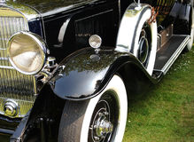 Classic Car. Shiny black fenders, running board, whitewall tires, chrome, parked on green grass royalty free stock photos