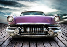 Classic car. An old classic American Pontiac Chieftain car with a chrome gill on a boardwalk with a cloudy background