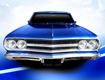 Classic car. Bright blue Chevrolet Malibu classic car. The vintage vehicle is on a blue surface with a light cloudy sky royalty free stock photo