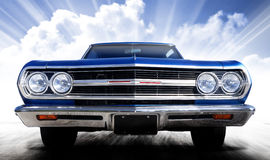 Classic car. Bright blue Chevrolet Malibu classic car. The vintage vehicle is on a blue surface with a light cloudy sky and streaks of light. This is a series royalty free stock photo