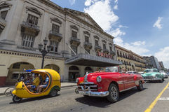 Classic car and Cocotaxi in Cuba. A red american classic car and Cocotaxi with tourists in Old Havana Stock Photos