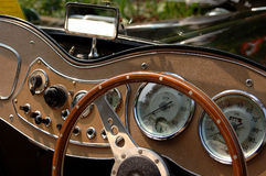 Classic car dashboard. A classic car's dashboard showing the speedometer, a tachometer and various other dials, switches and buttons. There is also a steering royalty free stock photo
