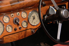 Classic car dashboard. A classic car's dashboard showing the steering wheel, speedometer, and various other dials, switches and buttons. The dashboard is made of stock photo