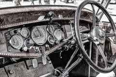 Classic car dashboard. Classic car wooden dashboard with black driving wheel on the right hand side Royalty Free Stock Images