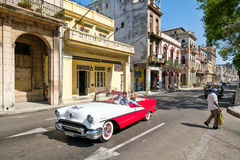 Classic car driving tourists along a famous Old Havana avenue Royalty Free Stock Images