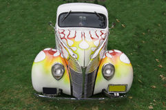 Classic Car With Flames. A white car with a flame design on the front sitting on grass Stock Image