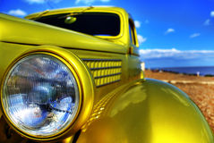 Classic car head lamp. Closeup of a classic car on the beach Stock Image
