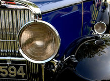 Classic Car Headlight. Round headlight is focus on the front of this classic blue automobile. Chrome and shiny blue paint job surround this object royalty free stock image