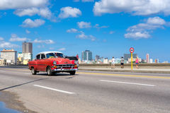 Classic car on the malecon avenue in Havana. HAVANA,CUBA - JULY 14,2016 : Classic car on the Havana malecon avenue with a view of the city skyline Stock Photo