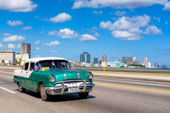 Classic car on the malecon avenue in Havana. HAVANA,CUBA - JULY 14,2016 : Classic car on the Havana malecon avenue with a view of the sea and the city skyline Royalty Free Stock Image