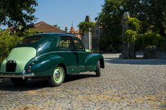Classic car parked in front of a garden gate Royalty Free Stock Images