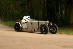 Classic car racing. Old classic car racing, with a crew of two in modern safety helmets Royalty Free Stock Photo