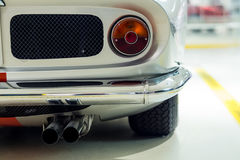Classic car rear details. Rear view of classic car. Detailed view of tail light, chrome bumper and twin exhaust Royalty Free Stock Image
