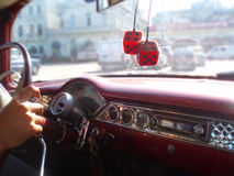 Classic car ride through Havana Cuba. Gleaming chrome and retro dice of the dashboard of classic car available for hire for city tour of Havana Cuba Royalty Free Stock Photo