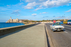 A classic car rides along the Malecon in Havana with El Morro castle on the background. HAVANA,CUBA - FEBRUARY 15,2017 : A classic vintage car rides along the Stock Photos
