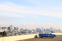Classic car in San Francisco, CA. Classic blue car in San Francisco with blue sky over the downtown in background Stock Photos