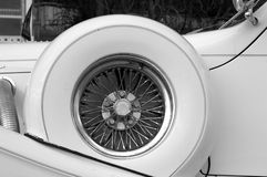 Classic car spare wheel. Detail of spare wheel оn white Excalibur classic car Stock Images