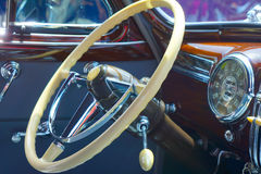 Classic Car steering wheel. Interior of classic car close up of steering wheel and dashboard. Notice the look of imitation ivory in the gears and levers and the royalty free stock image