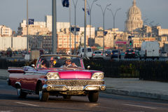 Classic car travels along the Malecon avenue in Havana with the Capitol building on the background. HAVANA,CUBA - FEBRUARY 24,2017 : A classic american car Royalty Free Stock Image