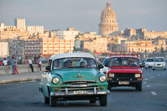 Classic car travels along the Malecon avenue in Havana with the Capitol building on the background. HAVANA,CUBA - FEBRUARY 24,2017 : A classic american car Stock Photo