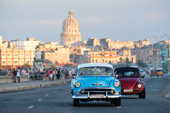 Classic car travels along the Malecon avenue in Havana with the Capitol building on the background. HAVANA,CUBA - FEBRUARY 24,2017 : A classic american car Stock Photos