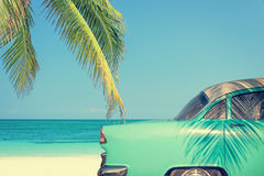Classic car on a tropical beach with palm tree Royalty Free Stock Photos
