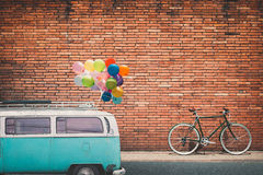 Classic car vintage van in city with colorful balloon on roof parked on road in urban. Concept of love in summer and wedding, honeymoon. flim grain filter Royalty Free Stock Photos
