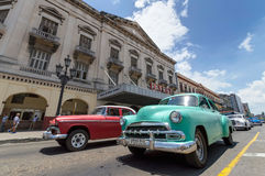 Classic cars in Cuba. Some classic american cars passing by the Payret theatre in Old Havana stock images