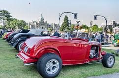 Classic cars on display in Victoria. Vintage cars are exhibited in Victoria, British Columbia with the parliament buildings of the provincial capital in the Stock Image