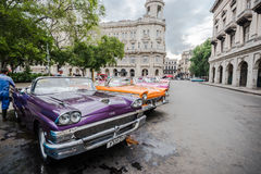 Classic cars park on street in Havana, Cuba. Stock Photos