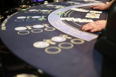 A classic casino blackjack table. Classic casino blackjack table with a dealer dealing hands and some cards and chips on it Stock Images