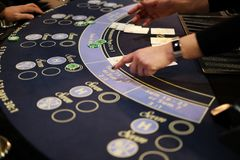Classic casino blackjack table with dealer. Player, chips and cards on the foreground Stock Image