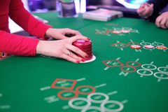 A classic casino craps table. Classic casino craps table with a dealer dealing hands, player making bets and some chips Stock Photo