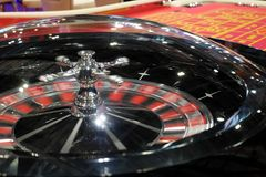 Classic casino roulette game and table in the background. Classic casino roulette game with spinning wheel and a red table in the background Stock Photo