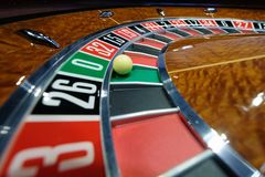 Classic casino roulette wheel with ball on number 0 green. A classic casino roulette wheel with ball stopped on number 0 green close-up shot Royalty Free Stock Photo