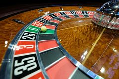 Classic casino roulette wheel with ball on number 0 green. A classic casino roulette wheel spinning with ball stopped on number 0 green close-up shot Stock Photos