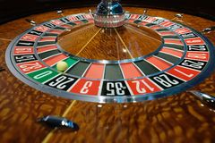 Classic casino roulette wheel with ball on number 0 green. A classic casino roulette wheel spinning with ball stopped on number 0 green wide shot Stock Photos