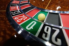 Classic casino roulette wheel with ball on number 0 green. A classic casino roulette wheel spinning with ball stopped on number 0 green close-up shot Stock Images