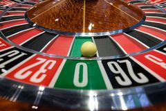 Classic casino roulette wheel with ball on number 0 green. A classic casino roulette wheel spinning with ball stopped on number 0 green close-up shot Royalty Free Stock Photos