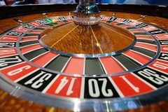 Classic casino roulette wheel with ball on number 0 green. A classic casino roulette wheel with ball stopped on number 0 green close-up shot Stock Photos