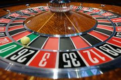 Classic casino roulette wheel with ball on number 0 green. A classic casino roulette wheel with ball stopped on number 0 green close-up shot Royalty Free Stock Photography