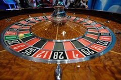 Classic casino roulette wheel with ball on number 0 green. A classic casino roulette wheel with ball stopped on number 0 green close-up shot Royalty Free Stock Images