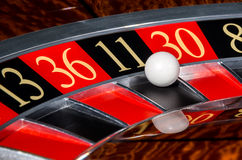 Classic casino roulette wheel with black sector eleven 11. And white ball and sectors 13, 36, 30, 8 stock image