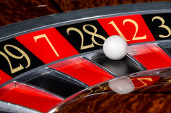 Classic casino roulette wheel with black sector twenty-eight 28. And white ball and sectors 29, 7, 12, 35 Stock Image