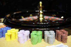 Classic casino roulette wheel and chips. A classic casino roulette wheel and piles of chips on the front Royalty Free Stock Photo